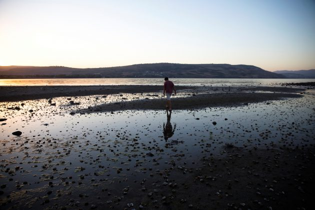 A man walks towards an island that has materialized at the southern edge of the Sea of Galilee in northern Israel November 1, 2018. Picture taken November 1, 2018. REUTERS/Ronen Zvulun
