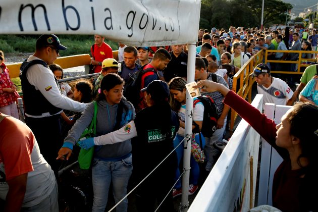 FILE PHOTO: Colombian migration officers check the identity documents of people trying to enter Colombia from Venezuela, at the Simon Bolivar International bridge in Villa del Rosario, Colombia August 25, 2018. REUTERS/Carlos Garcia Rawlins/File Photo