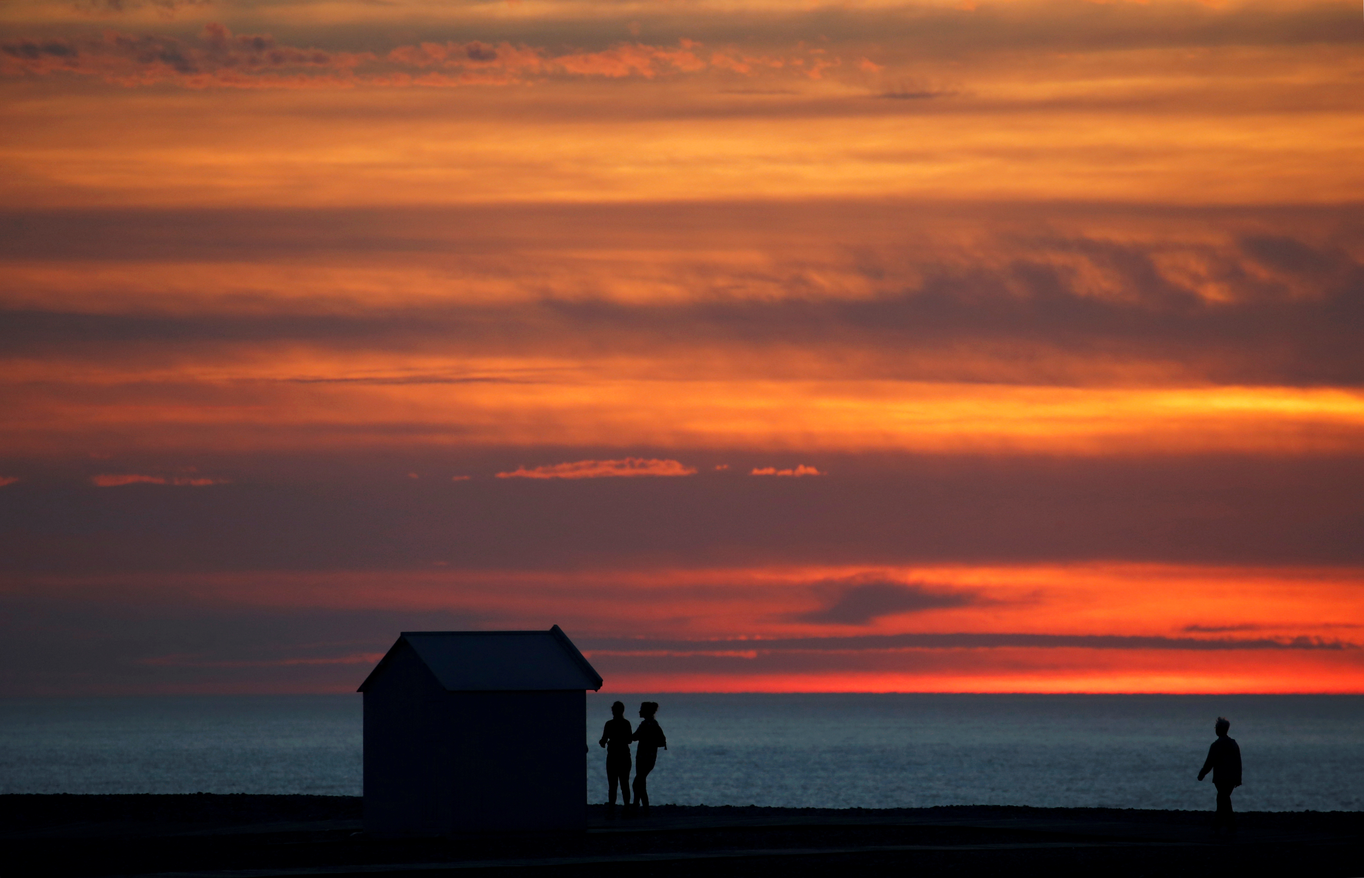 FILE PHOTO: People enjoy a walk at sunset past beach cabin on the pebbled beach in Cayeux-sur-Mer, France, October 13, 2018. REUTERS/Pascal Rossignol/File Photo
