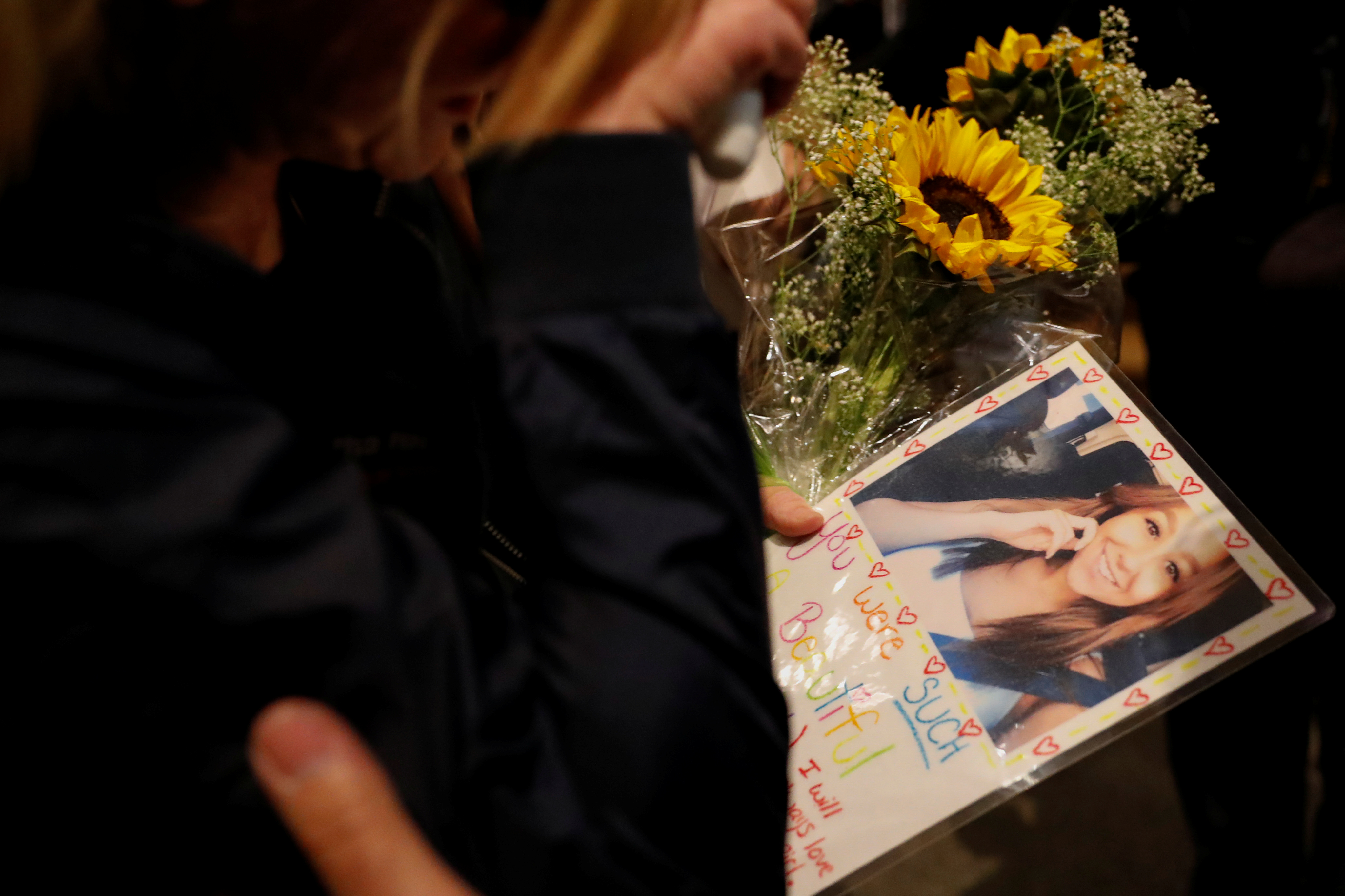 A mourner arrives with a picture of one of her friends at a vigil for the victims of the mass shooting, at the Thousand Oaks Civic Arts Plaza in Thousand Oaks, California, U.S., November 8, 2018. REUTERS/Mike Blake NO RESALES. NO ARCHIVES
