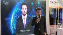 Xinhua news anchor Qiu Hao stands next to an AI virtual news anchor based on him, at a Sogou booth during an expo at the fifth World Internet Conference (WIC) in Wuzhen town of Jiaxing, Zhejiang province, China November 7, 2018. Picture taken November 7, 2018. E Xiaoying/Qianlong.com via REUTERS