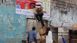 FILE PHOTO - Workers fix an Ebola awareness poster in Tchomia, Democratic Republic of Congo, to raise awareness about Ebola in the local community, on October 9, 2018. Picture taken October 9, 2018. WHO/Aboulaye Cisse/Handout via REUTERS