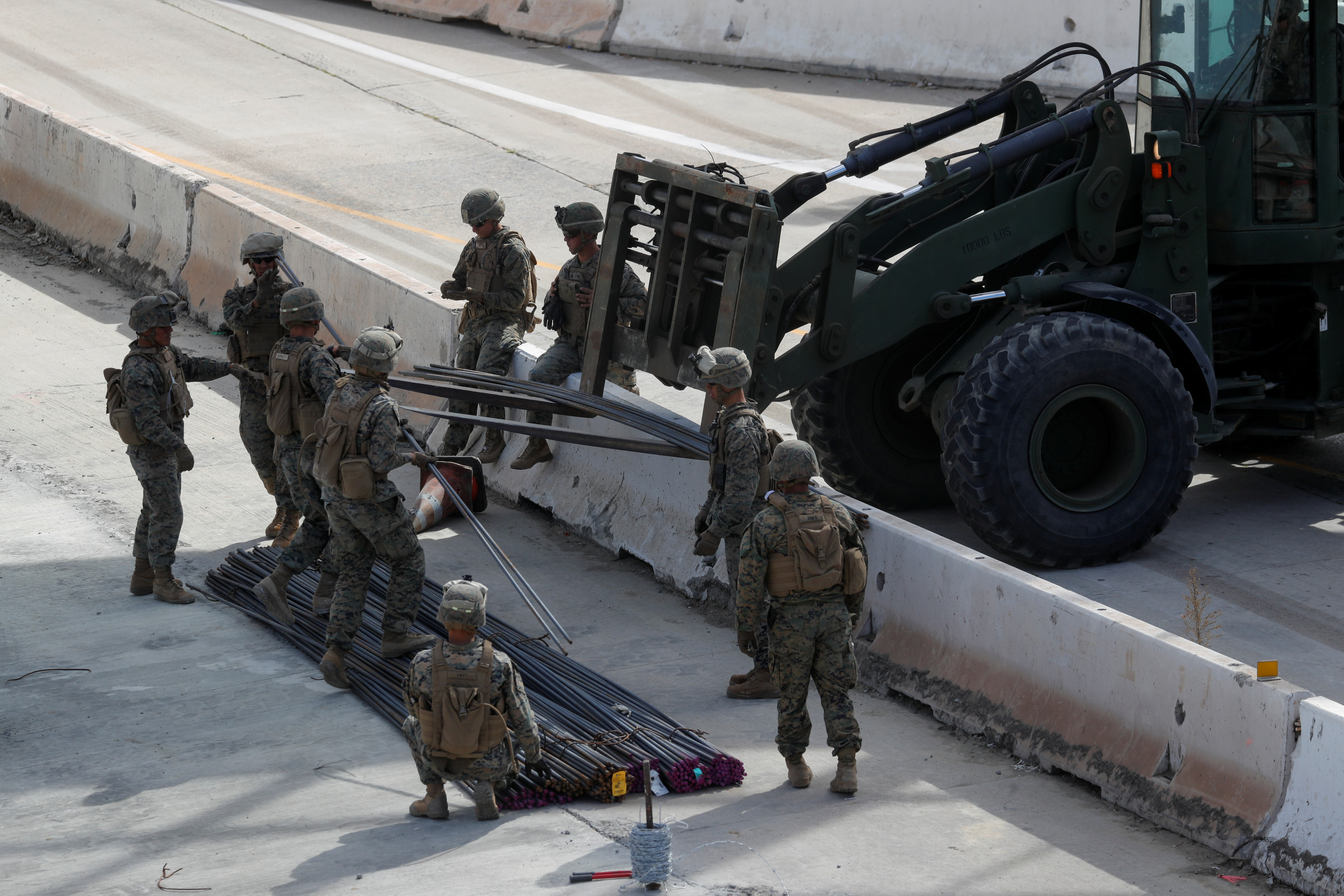 U.S. Marines work to move building materials as they harden the border with Mexico in preparation for the arrival of a caravan of migrants at the San Ysidro border crossing in San Diego, California, U.S., November 13, 2018. REUTERS/Mike Blake