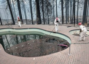 Forensic investigators search a community swimming pool for victims of the Camp Fire in Paradise, California, U.S., November 13, 2018. REUTERS/Noel Randewich