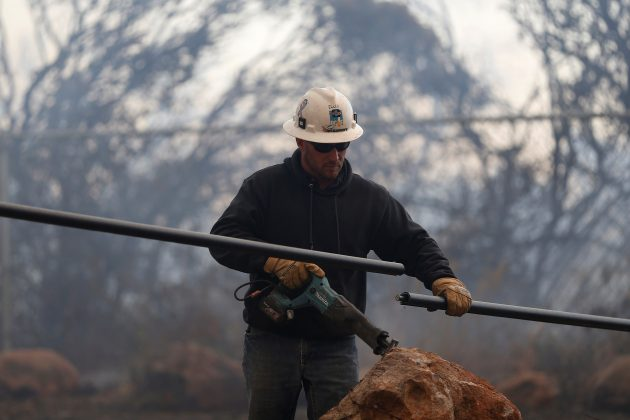 A Pacific Gas & Electric lineman cuts a downed power line during the Camp Fire in Paradise, California, U.S. November 8, 2018. REUTERS/Stephen Lam