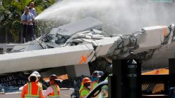 Firefighters spray water on debris from a collapsed pedestrian bridge at Florida International University in Miami, Florida, U.S., March 16, 2018. REUTERS/Joe Skipper