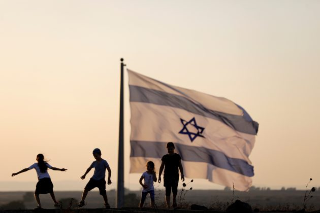 FILE PHOTO - Israeli kids play next to an Israeli flag next to the Israeli Syrian border at the Israeli-occupied Golan Heights, Israel July 23, 2018. REUTERS/Ronen Zvulun