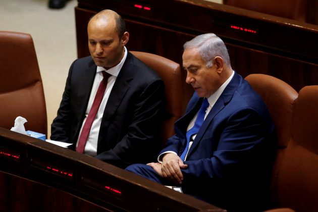 FILE PHOTO: Israeli Prime Minister Benjamin Netanyahu sits next to Israeli Education Minister Naftali Bennett during a session of the plenum of the Knesset, the Israeli Parliament, in Jerusalem, March 12, 2018. REUTERS/Ronen Zvulun/File Photo