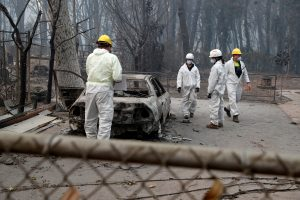 Members of a volunteer search and rescue team from Marin County search for human remains in a car destroyed by the Camp Fire in Paradise, California, U.S., November 14, 2018. REUTERS/Terray Sylvester
