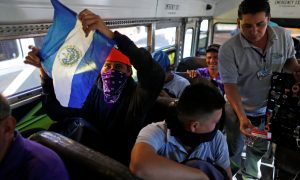 People in a caravan of migrants departing from El Salvador en route to the United States sit on a bus, in San Salvador, El Salvador, November 18, 2018. REUTERS/Jose Cabezas