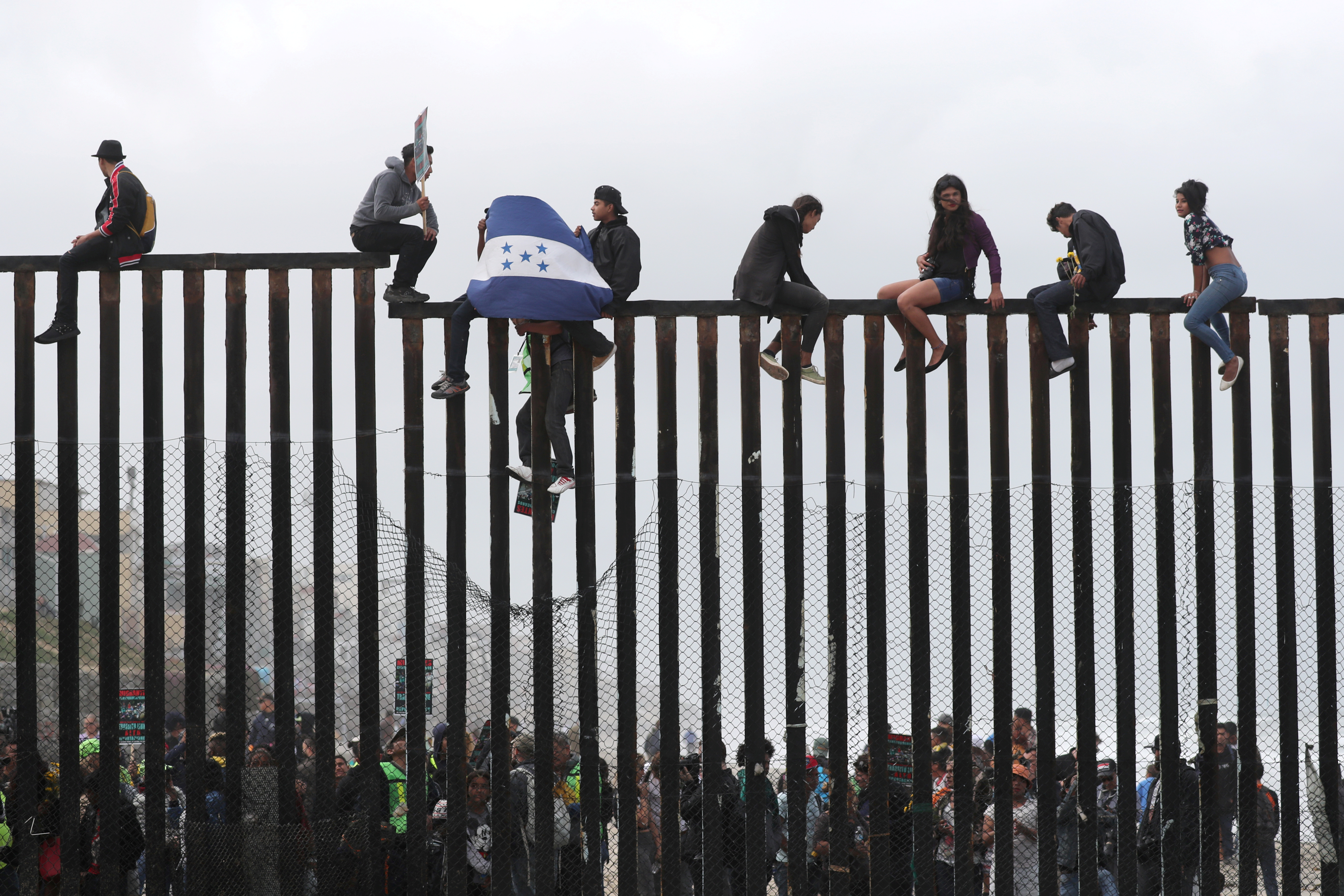 FILE PHOTO: Members of a migrant caravan from Central America and their supporters sit on the top of the U.S.-Mexico border wall at Border Field State Park before making an asylum request, in San Diego, California, U.S. April 29, 2018. REUTERS/Lucy Nicholson/File Photo