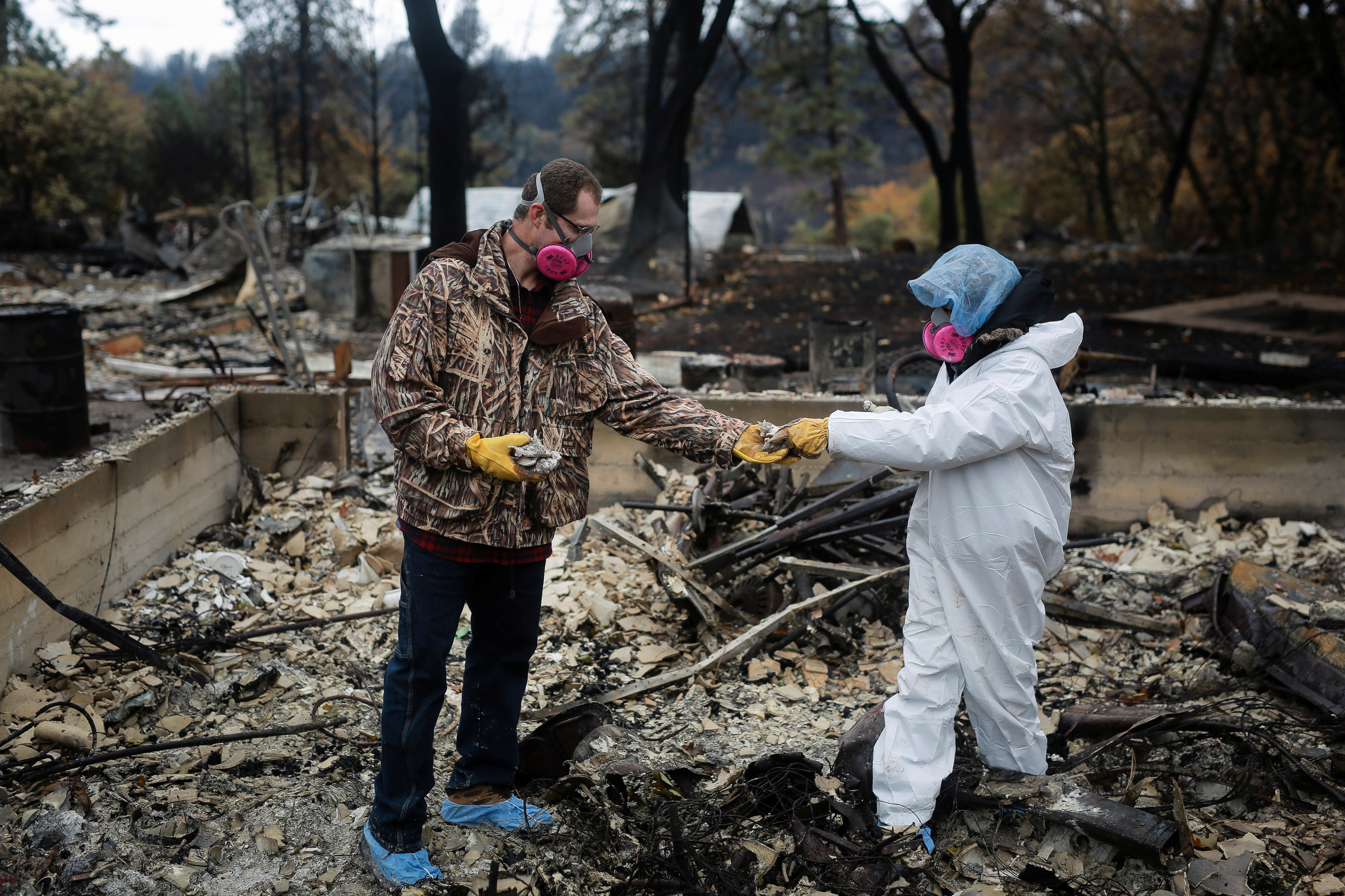 Vanthy Bizzle hands some small religious figurines to her husband Brett Bizzle in the remains of their home after returning for the first time since the Camp Fire forced them to evacuate in Paradise, California, U.S. November 22, 2018. REUTERS/Elijah Nouvelage