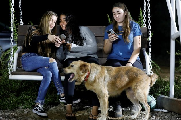 Israeli teens, Meshy Elmkies (R), 16, Liam Yefet (C), 16 and Lee Cohen, 17, co-managers of Instagram account, Otef.Gaza, look at their mobile phones as they sit on a swing at Kibbutz Kerem Shalom which borders the Gaza Strip, in southern Israel November 11, 2018. Picture taken November 11, 2018. REUTERS/Amir Cohen