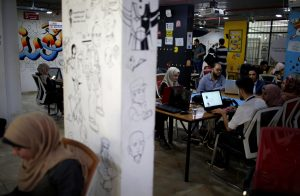 Members of 'We Are Not Numbers' team work on laptops in an office in Gaza City November 7, 2018. Picture taken November 7, 2018. REUTERS/Mohammed Salem