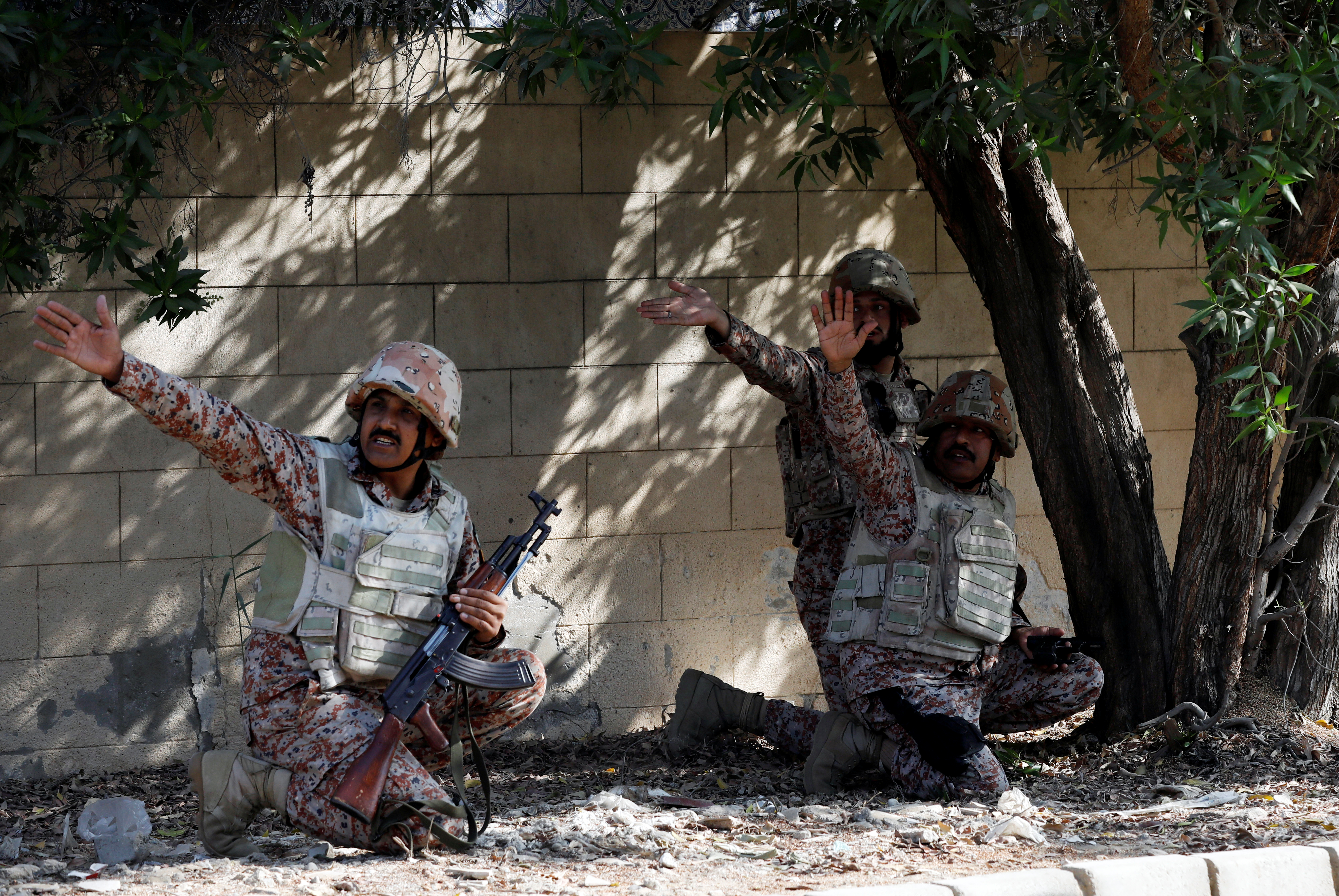 Paramilitary soldiers take cover behind a wall during an attack on the Chinese consulate, where blasts and shots are heard, in Karachi, Pakistan November 23, 2018. REUTERS/Akhtar Soomro