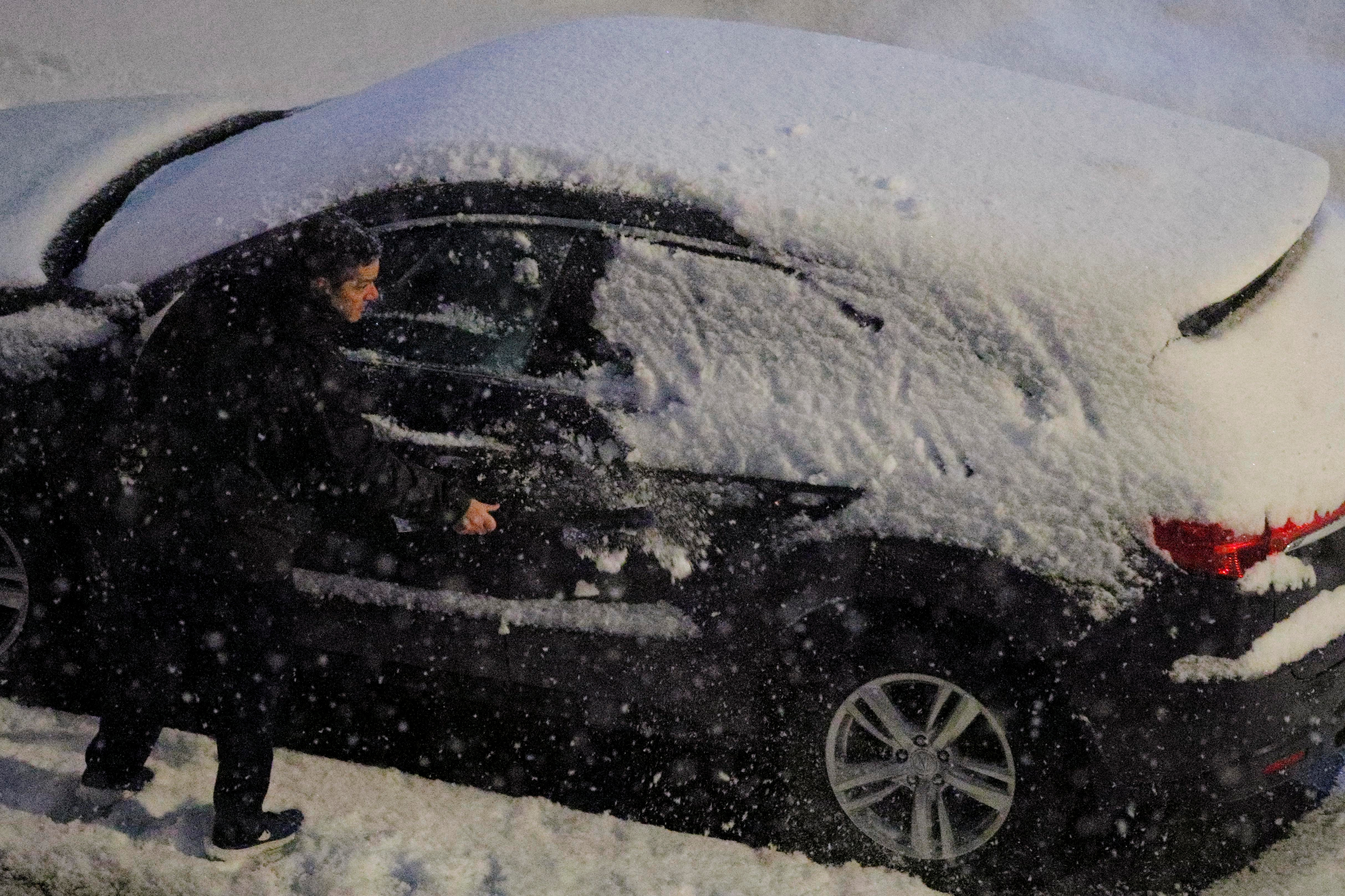 A driver clears the snow off his car during an early season snowfall in the Boston suburb of Medford, Massachusetts, U.S., November 15, 2018. REUTERS/Brian Snyder