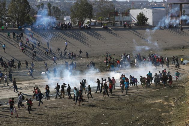Migrants run from tear gas, thrown by the U.S border patrol, near the border fence between Mexico and the United States in Tijuana, Mexico, November 25, 2018. REUTERS/Hannah McKay