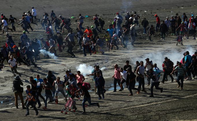 FILE PHOTO: Migrants, part of a caravan of thousands from Central America trying to reach the United States, run from tear gas released by U.S border patrol, near the border fence between Mexico and the United States in Tijuana, Mexico, November 25, 2018. REUTERS/Hannah McKay