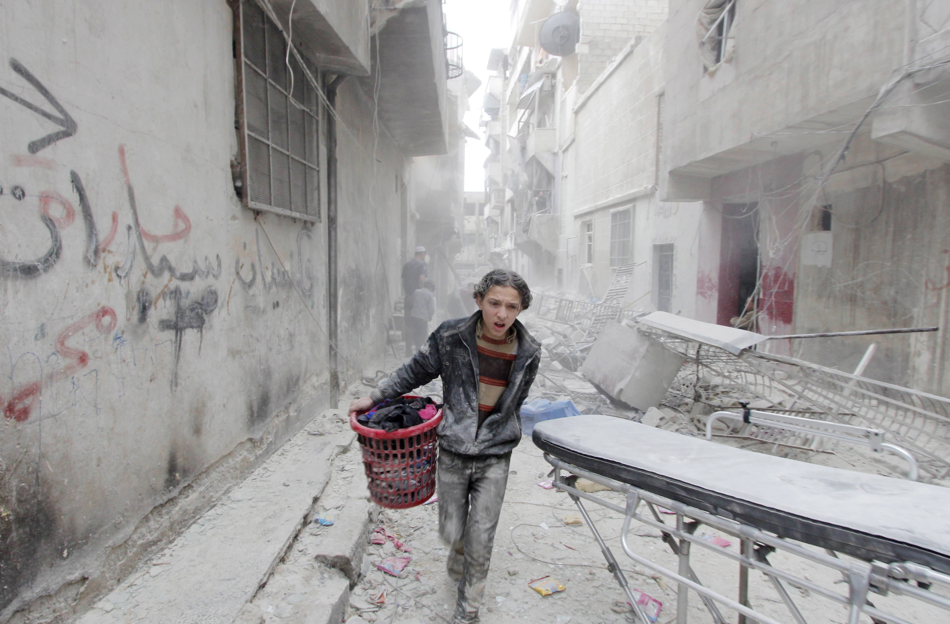FILE PHOTO: A boy carries his belongings at a site hit by what activists said was a barrel bomb dropped by forces loyal to Syria's President Bashar al-Assad in Aleppo's al-Fardous district, Syria April 2, 2015. REUTERS/Rami Zayat/File Photo