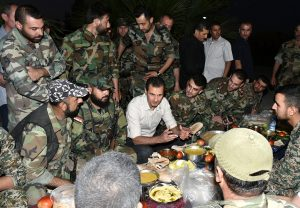 FILE PHOTO: Syria's president Bashar al-Assad (C) joins Syrian army soldiers for Iftar in the farms of Marj al-Sultan village, eastern Ghouta in Damascus, Syria in this handout picture provided by SANA on June 26, 2016./File Photo