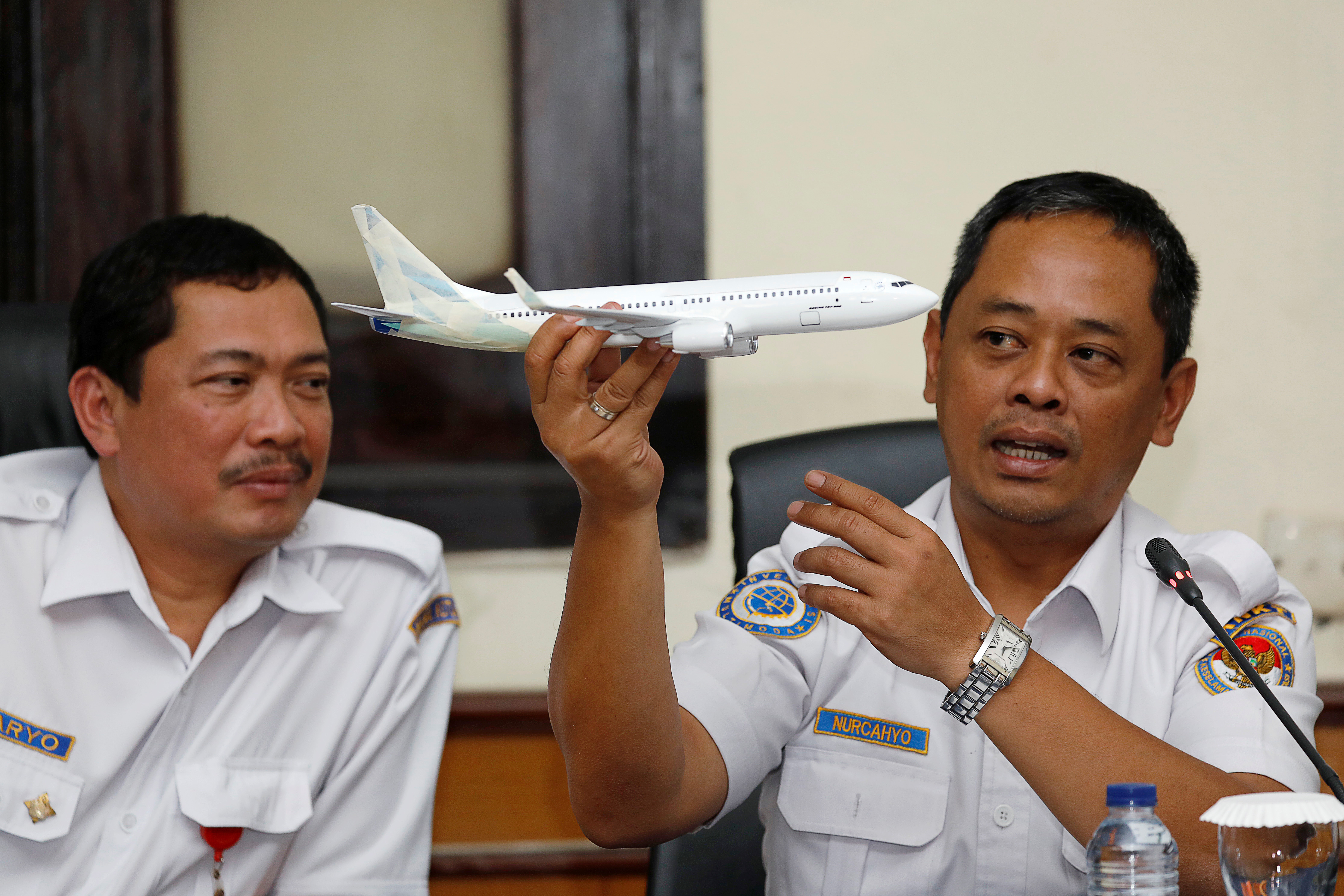 Indonesia's National Transportation Safety Committee (KNKT) sub-committee head for air accidents, Nurcahyo Utomo, holds a model airplane while speaking next to deputy chief of KNKT Haryo Satmiko during a news conference on its investigation into a Lion Air plane crash last month, in Jakarta, Indonesia November 28, 2018. REUTERS/Darren Whiteside