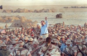 FILE PHOTO: U.S. President George H. W. Bush waves goodbye to U.S. Marines and members of the British 7th Armoured Brigade as they conclude a Thanksgiving Day visit with troops in the Saudi desert November 22, 1990. REUTERS/Rick Wilking/File Photo