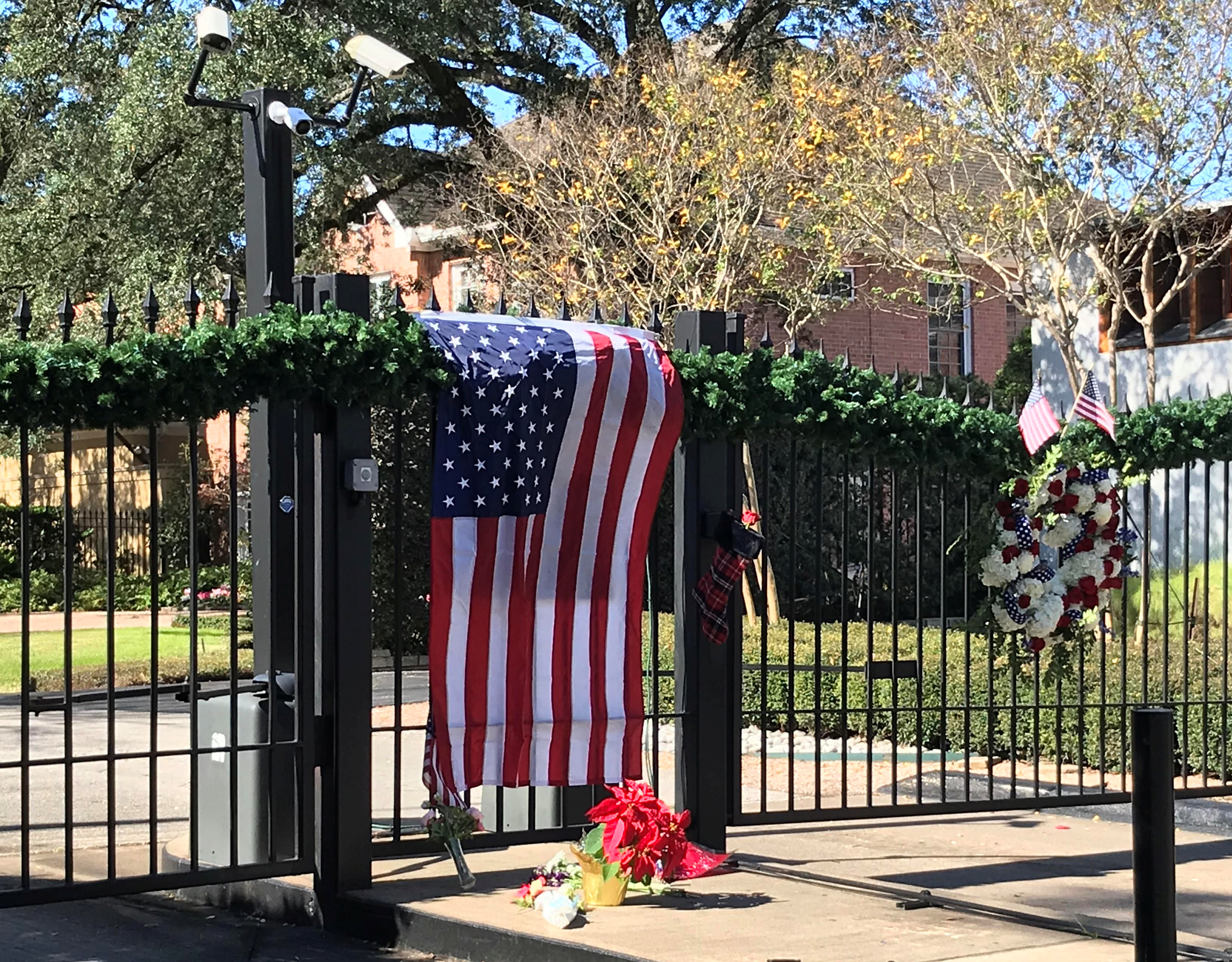 A flag is draped over the gate to the neighborhood of the home of former President George H.W. Bush, a day after he passed away in Houston, Texas, U.S. December 1, 2018. REUTERS/Gary McWilliams