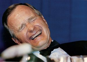 FILE PHOTO: U.S. President George H.W. Bush laughs while attending the annual White House Correspondents Association Awards dinner in Washington May 21, 1988. REUTERS/Stelios Varias/File Photo