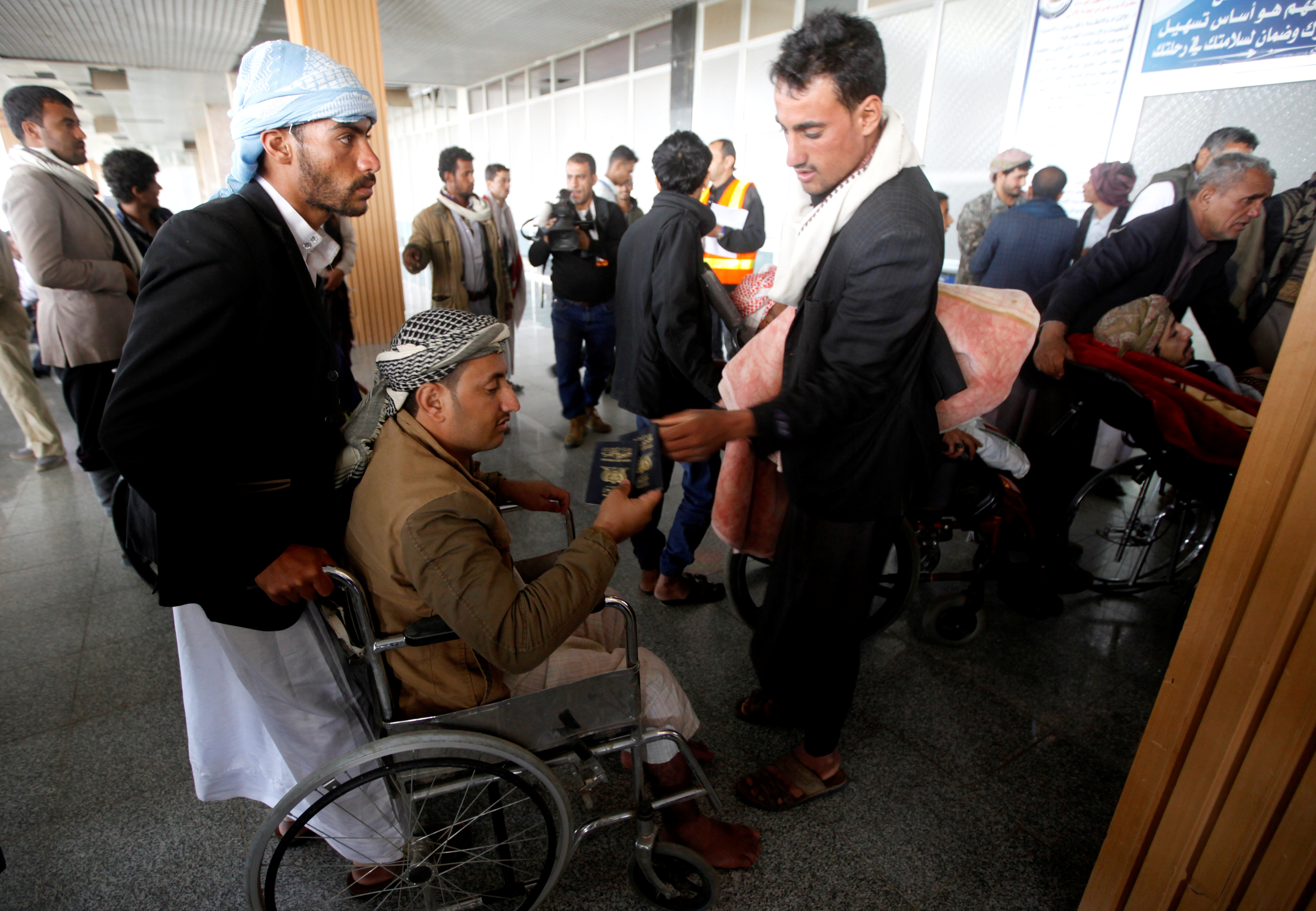 A wounded Houthi fighter, on a wheelchair, holds his passport at Sanaa airport during his evacuation from Yemen, December 3, 2018. REUTERS/Mohamed al-Sayaghi