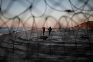 U.S. Customs and Border Protection (CBP) officials walk on the beach in San Diego County, U.S., as photographed through the border wall in Tijuana, Mexico, December 3, 2018 REUTERS/Alkis Konstantinidis
