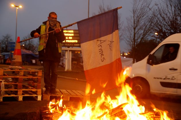 A protester wearing a yellow vest, the symbol of a French drivers' protest against higher diesel fuel prices, holds a flag near burning debris at the approach to the A2 Paris-Brussels Motorway, in Fontaine-Notre-Dame, France, December 4, 2018. REUTERS/Pascal Rossignol