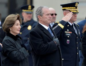 Former President George W. Bush places his hand over his heart with Laura Bush as they watch the casket of the late former President George H.W. Bush depart the U.S. Capitol enroute to the National Cathedral for funeral services, Washington, U.S., December 5, 2018. REUTERS/Mike Theiler