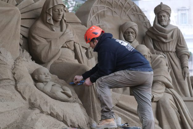 An artist works on a sand sculpture representing part of nativity scene in St. Peter's square at the Vatican, December 6, 2018. REUTERS/Alessandro Bianchi
