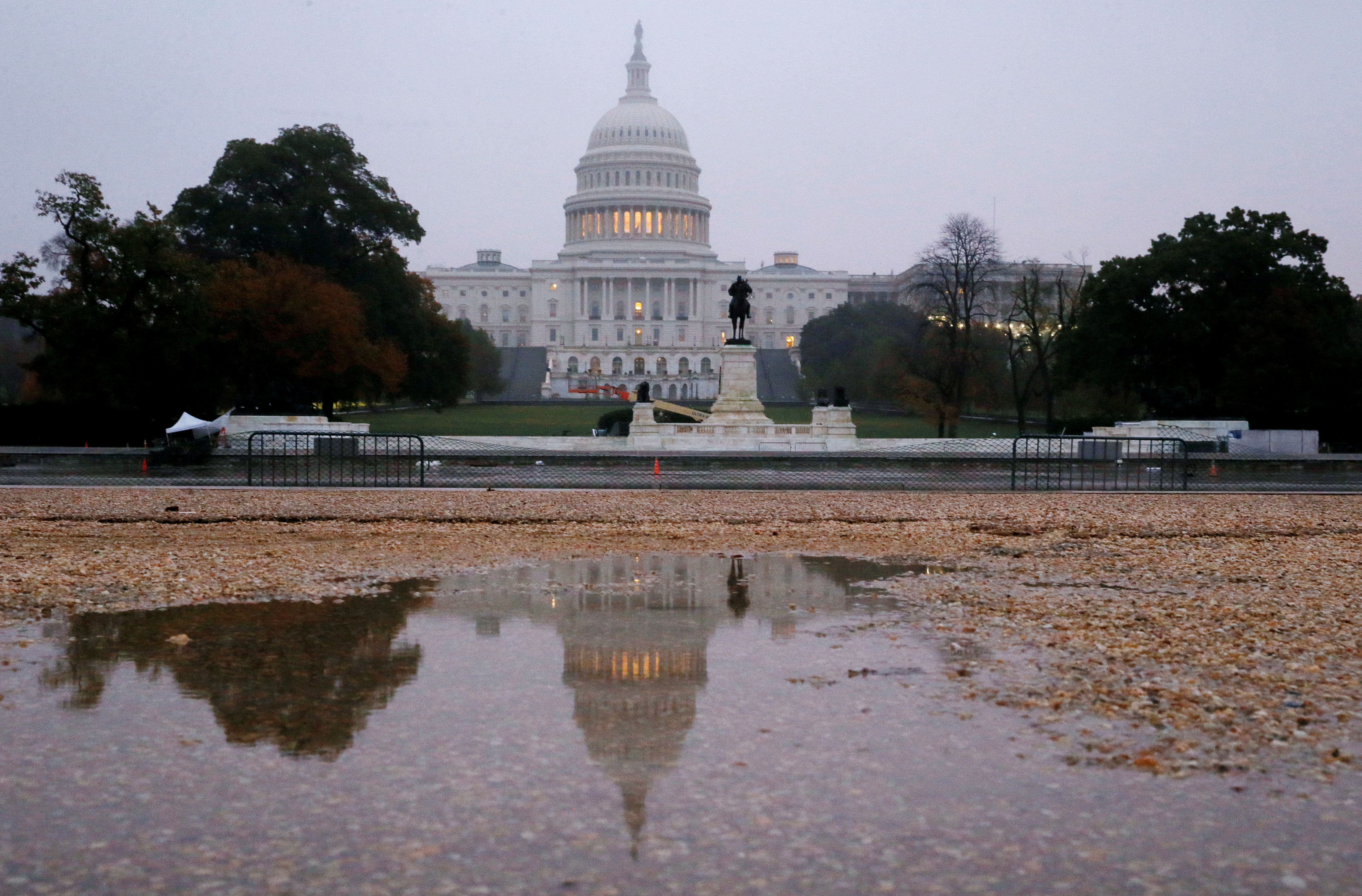 The U.S. Capitol building is seen reflected in a puddle at sunrise on the day of the U.S. midterm election as voters go to the polls across the country to elect 33 U.S. senators and all 435 members of the U.S. House of Representatives in Washington, U.S., November 6, 2018. REUTERS/Jim Bourg