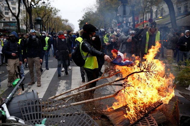 "Protesters wearing yellow vests install a barricade during clashes with police at a demonstration during a national day of protest by the ""yellow vests"" movement in Paris, France, December 8, 2018. REUTERS/Stephane Mahe"