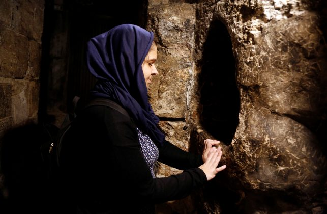 A tourist prays in the Church of the Nativity in Bethlehem, in the occupied West Bank, December 10, 2018. REUTERS/Raneen Sawafta