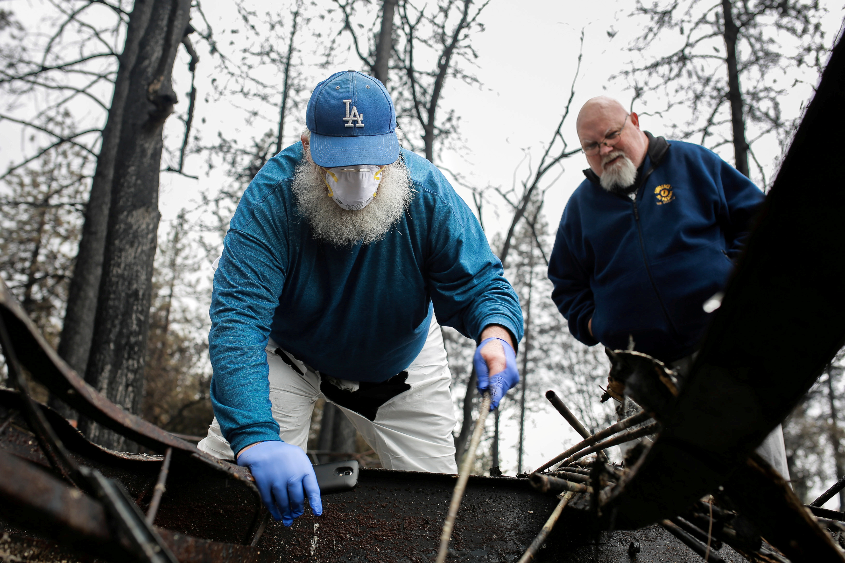FILE PHOTO: Stanley Miniszewski Sr. uses a burnt golf club to look for a pair of expensive dentures in the remains of his RV after returning for the first time since the Camp Fire forced him to evacuate as his friend Merrill Jackson looks on at Pine Ridge Park in Paradise, California, U.S. November 22, 2018. REUTERS/Elijah Nouvelage/File Photo
