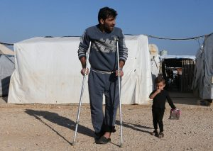 A Syrian refugee walks on crutches at a refugee camp in Akkar, northern Lebanon, November 27, 2018. Picture taken November 27, 2018. REUTERS/Mohamed Azakir