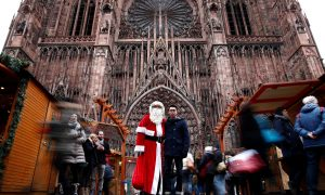A man dressed as Father Christmas poses with a tourist outside the Cathedral in Strasbourg, France, December 14, 2018. REUTERS/Christian Hartmann