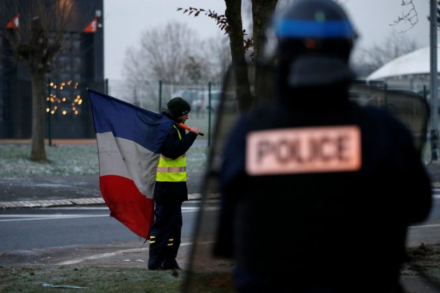 A protester wearing a yellow vest holds a French flag as the authorities dismantle their shelter at a traffic island near the A2 Paris-Brussels motorway in Fontaine-Notre-Dame, France, December 14, 2018. REUTERS/Pascal Rossignol
