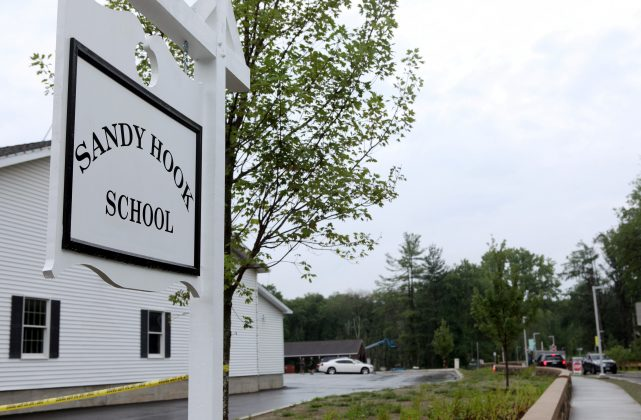 FILE PHOTO: The sign for the new Sandy Hook Elementary School at the end of the drive leading to the school is pictured in Newtown, Connecticut, U.S. July 29, 2016. REUTERS/Michelle McLoughlin/File Photo