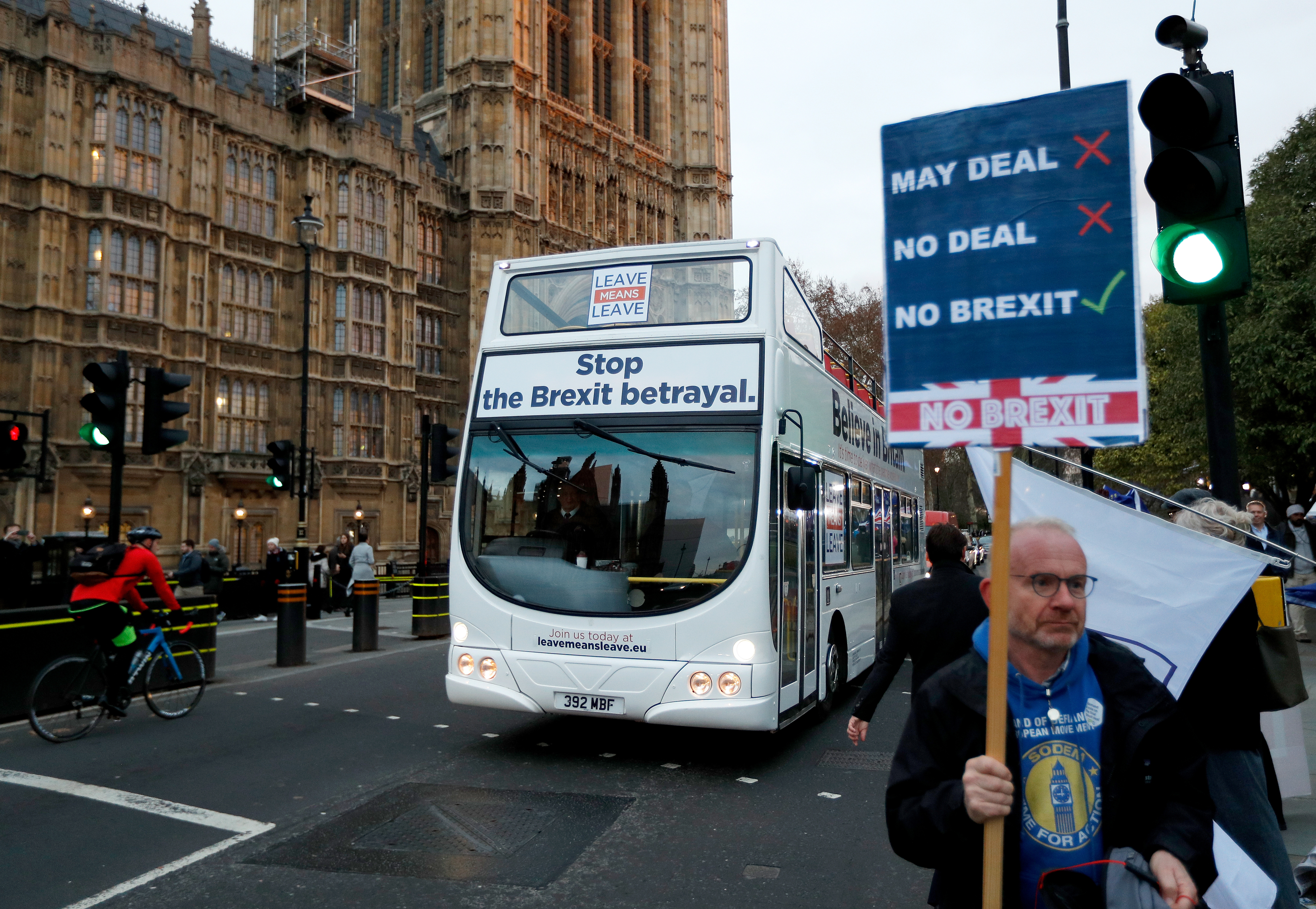 FILE PHOTO: A bus with a pro-Brexit message passes an anti-Brexit demonstrator outside the Houses of Parliament in London, Britain, December 10, 2018. REUTERS/Peter Nicholls