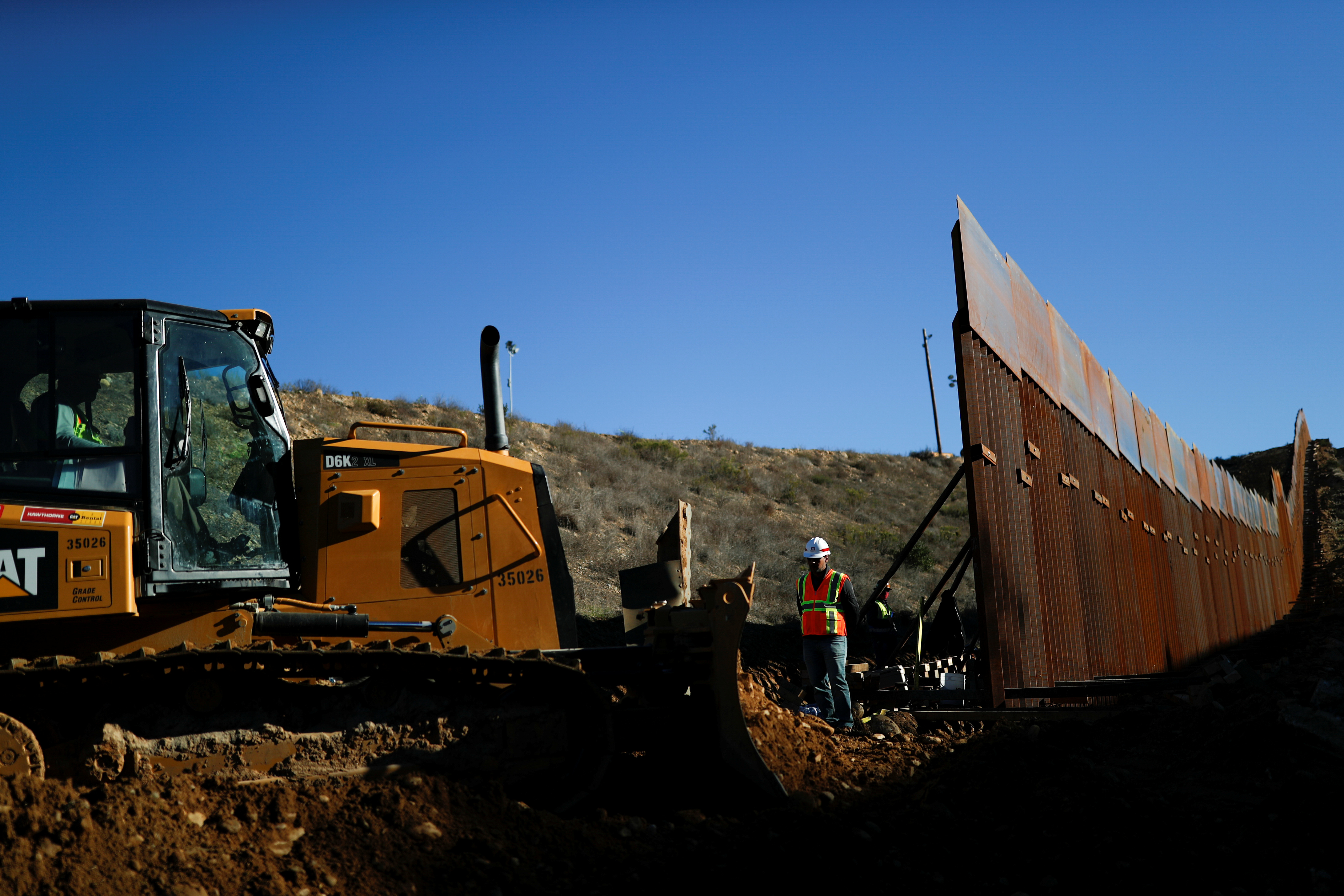 FILE PHOTO: Workers on the U.S. side, work on the border wall between Mexico and the U.S., as seen from Tijuana, Mexico, December 13, 2018. REUTERS/Carlos Garcia Rawlins