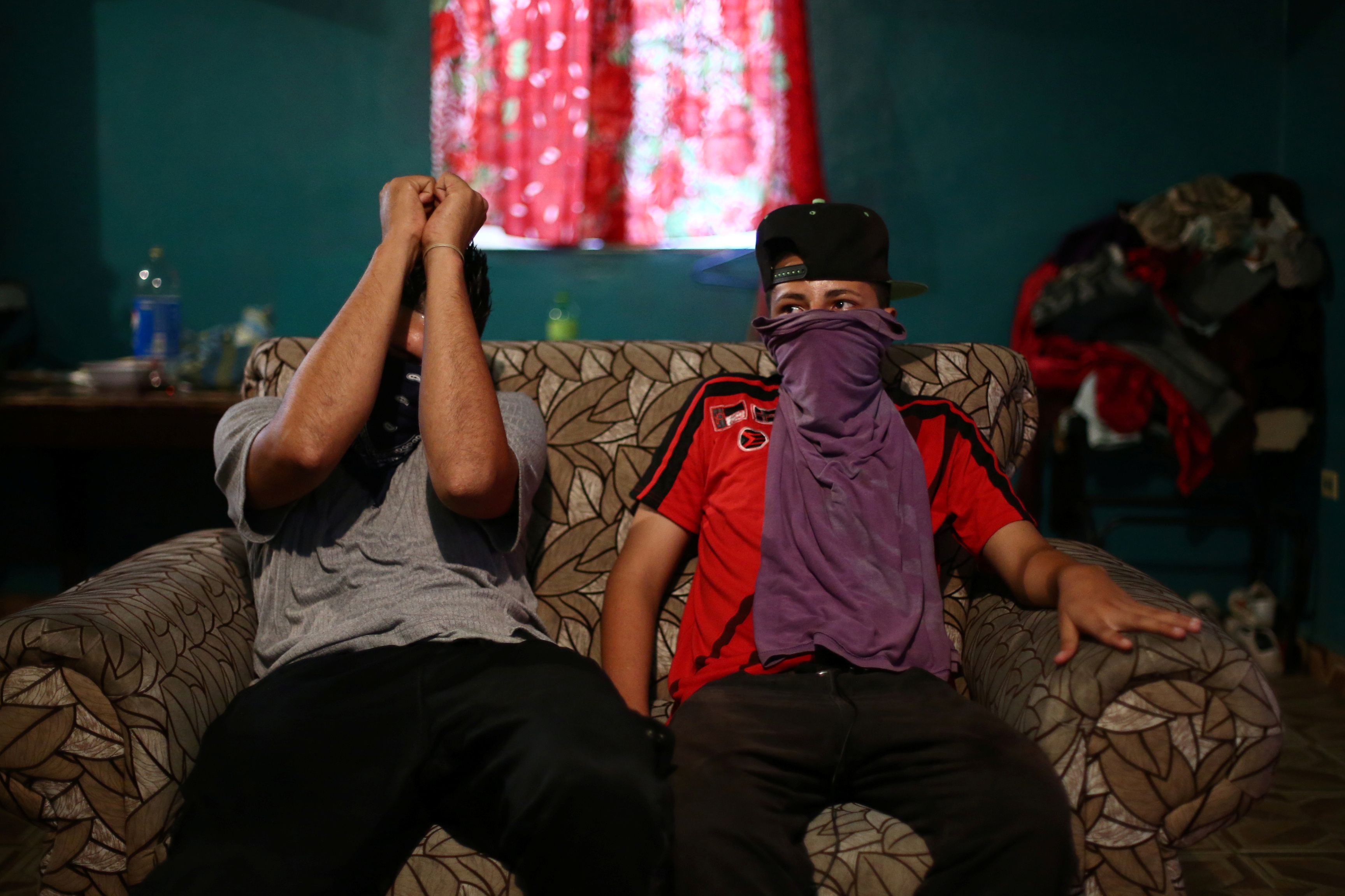 """El Fresa"" (L), a Barrio-18 gang member, sits on a sofa next to another Barrio-18 gang member in San Pedro Sula, Honduras, May 27, 2018. REUTERS/Edgard Garrido"