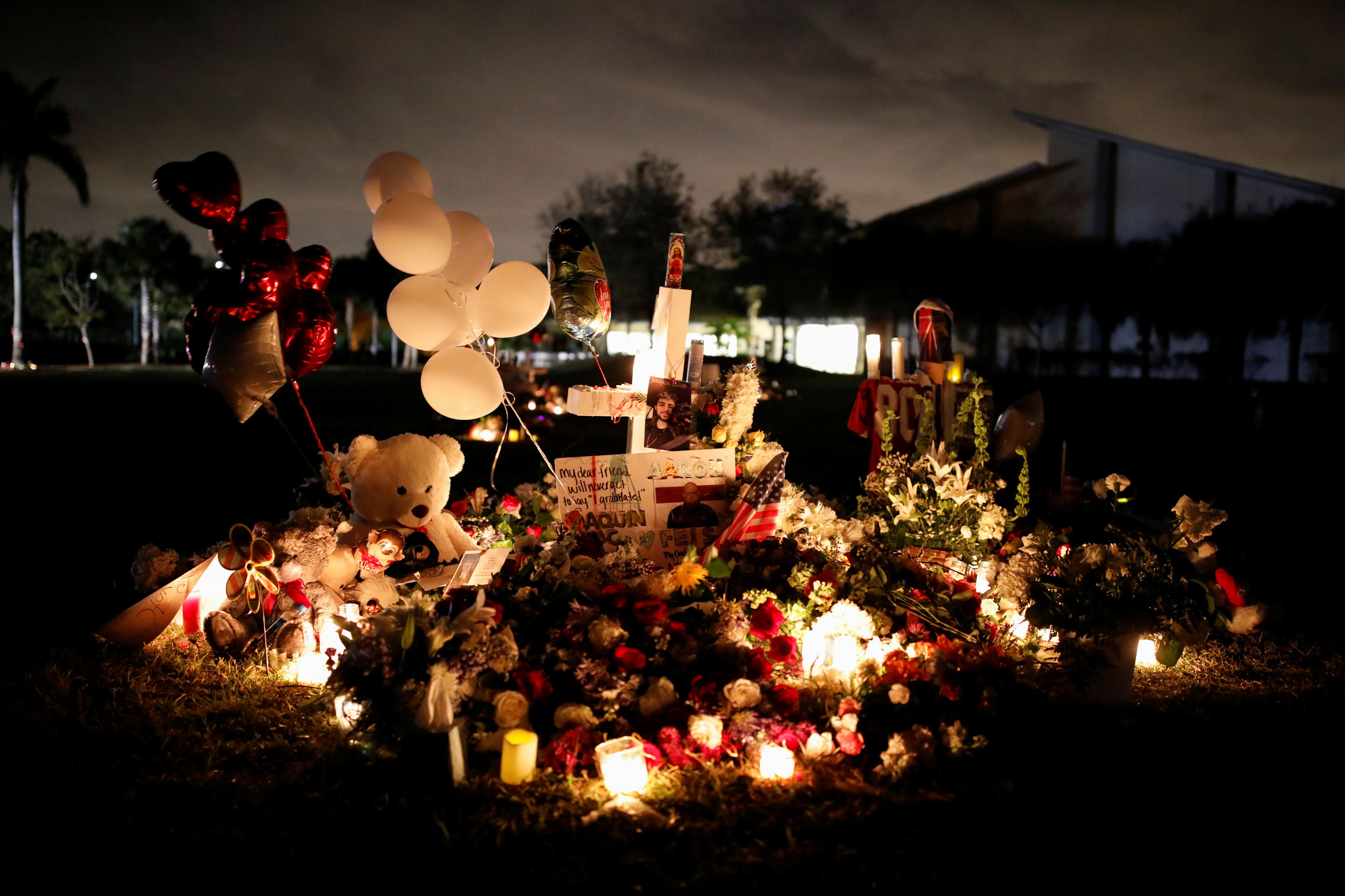 Pictures of Joaquin Oliver and Aaron Feis, victims of the mass shooting at Marjory Stoneman Douglas High School, are seen on a cross placed in a park to commemorate the victims, in Parkland, Florida, U.S., February 19, 2018. REUTERS/Carlos Garcia Rawlins