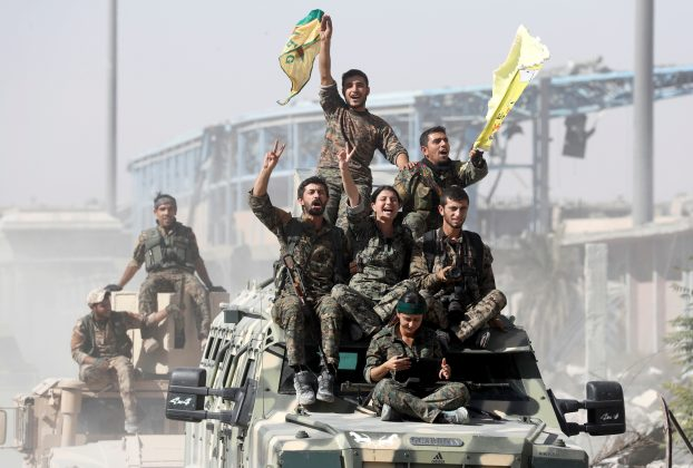 FILE PHOTO: Kurdish-led militiamen ride atop military vehicles as they celebrate victory over Islamic State in Raqqa, Syria, October 17, 2017. REUTERS/Erik De Castro/File Photo