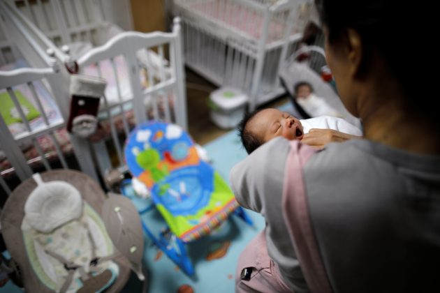 A volunteer takes care of a baby who was left in the baby box at Jusarang Community Church in Seoul, South Korea, December 18, 2018. REUTERS/Kim Hong-Ji
