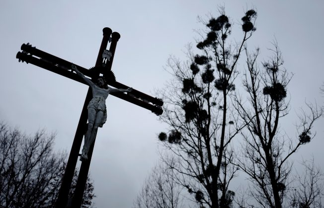 A cross is seen near trees with mistletoe near the church in Kalinowka, Poland November 25, 2018. Picture taken November 25, 2018. REUTERS/Kacper Pempel
