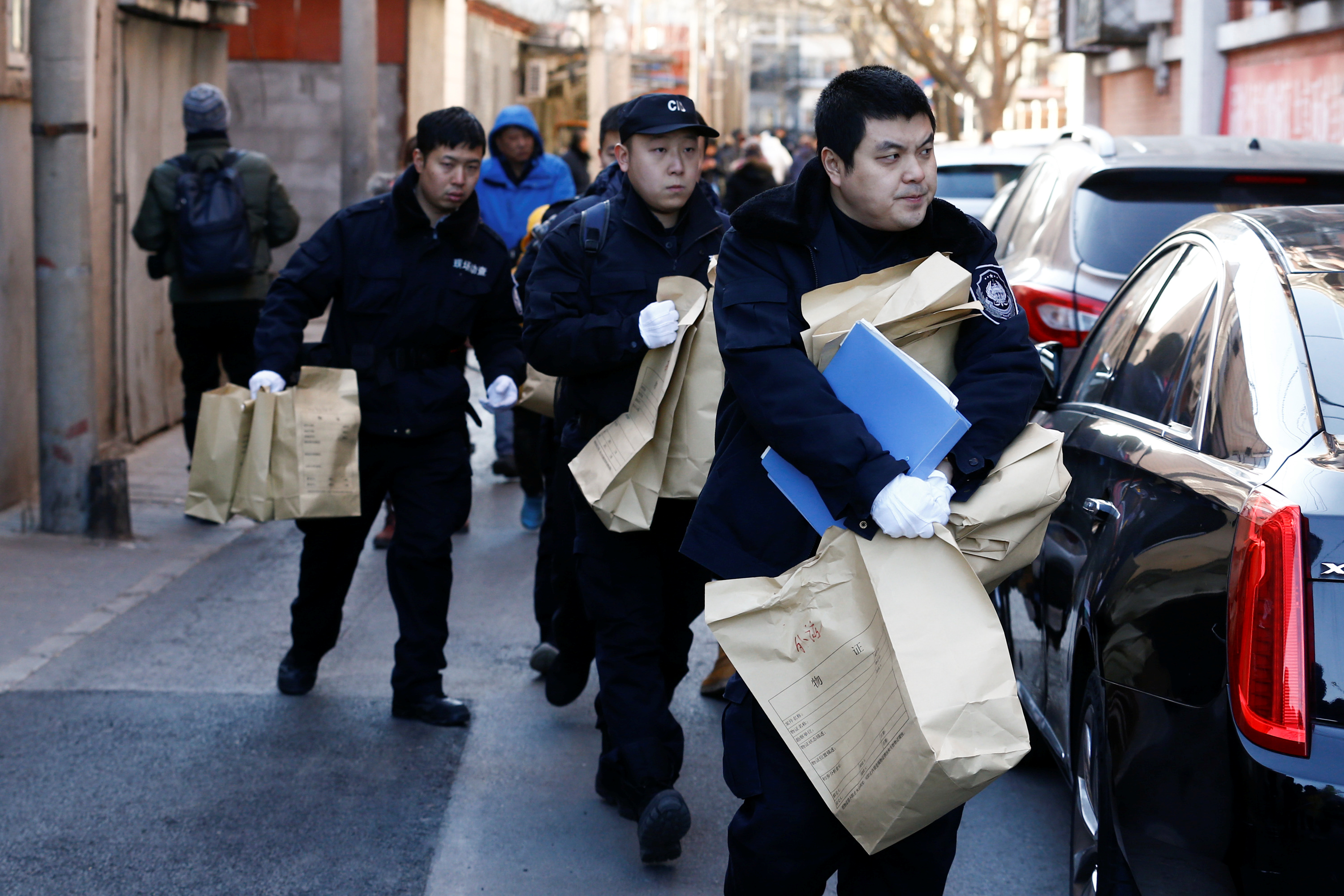 Police carry bags from a primary school that was the scene of a knife attack in Beijing, China, January 8, 2019. REUTERS/Thomas Peter
