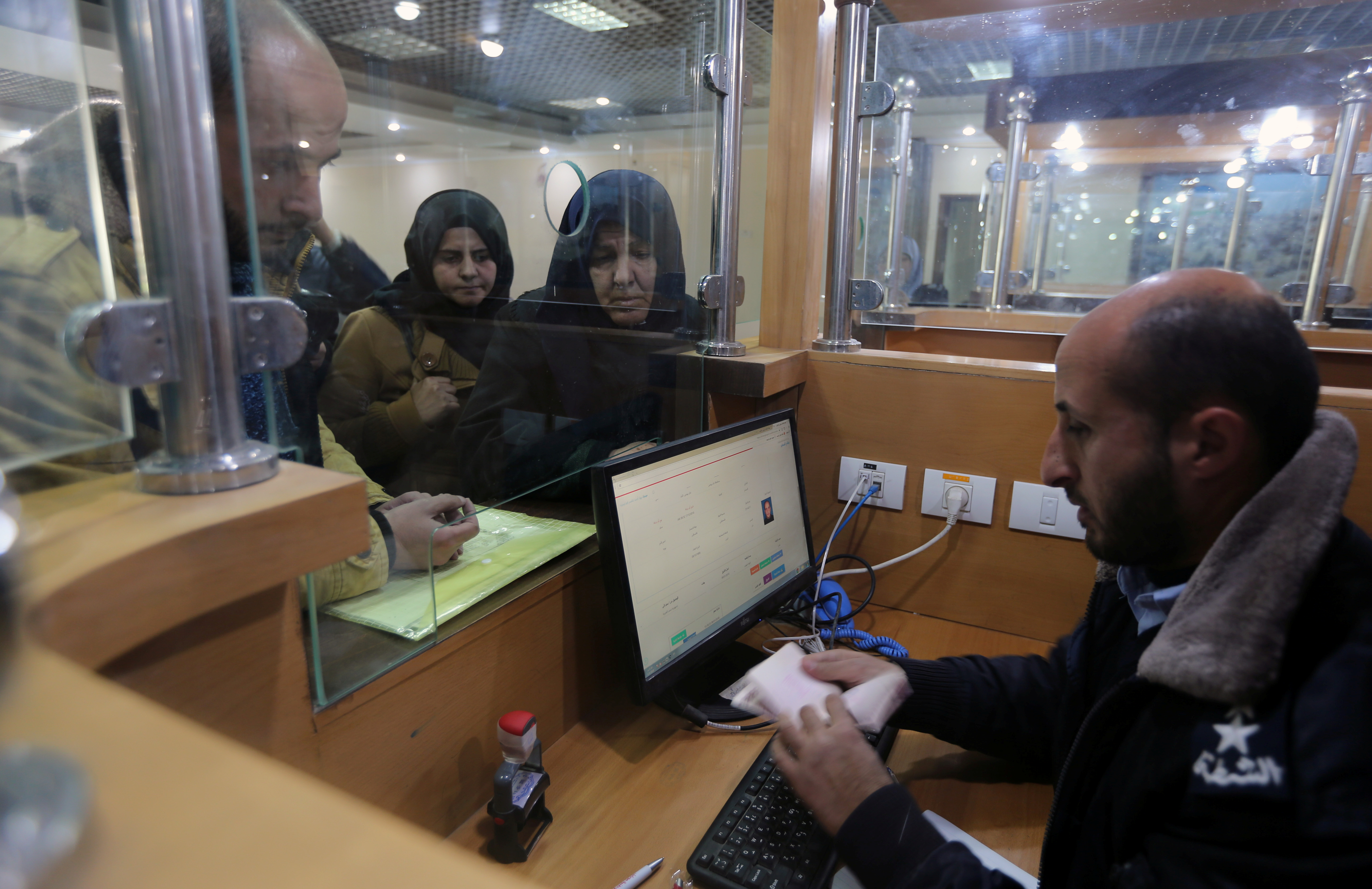 A Palestinian Hamas-hired police officer checks the documents of people upon their return from Egypt, at Rafah border crossing in the southern Gaza Strip January 8, 2019. REUTERS/Ibraheem Abu Mustafa